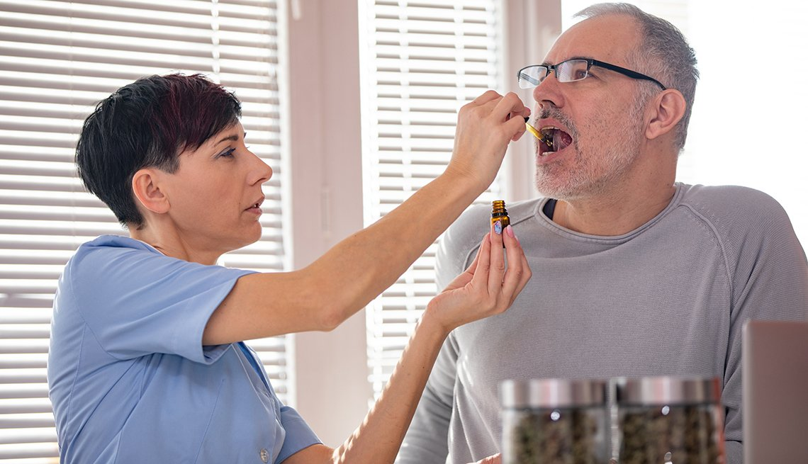 A woman putting a dropper of c b d marijuana oil into a mans mouth to help with pain