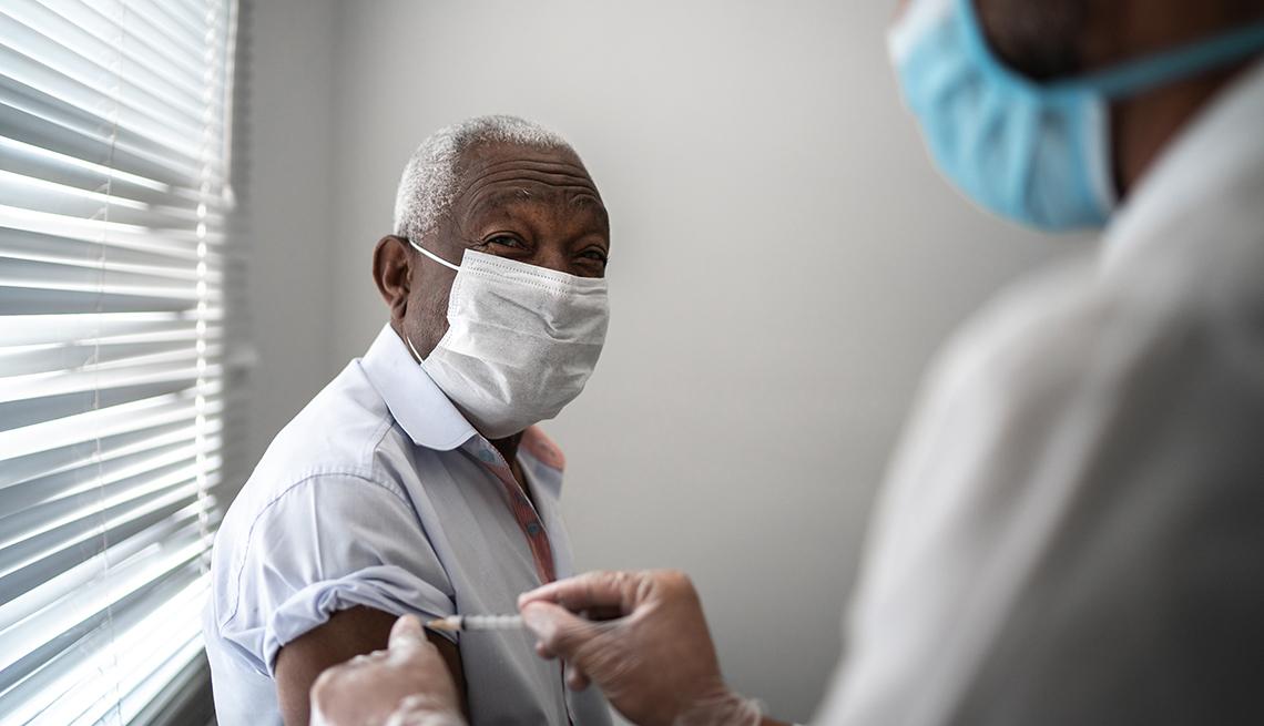 Una enfermera le pone a un residente de un hogar de ancianos una vacuna en el brazo.