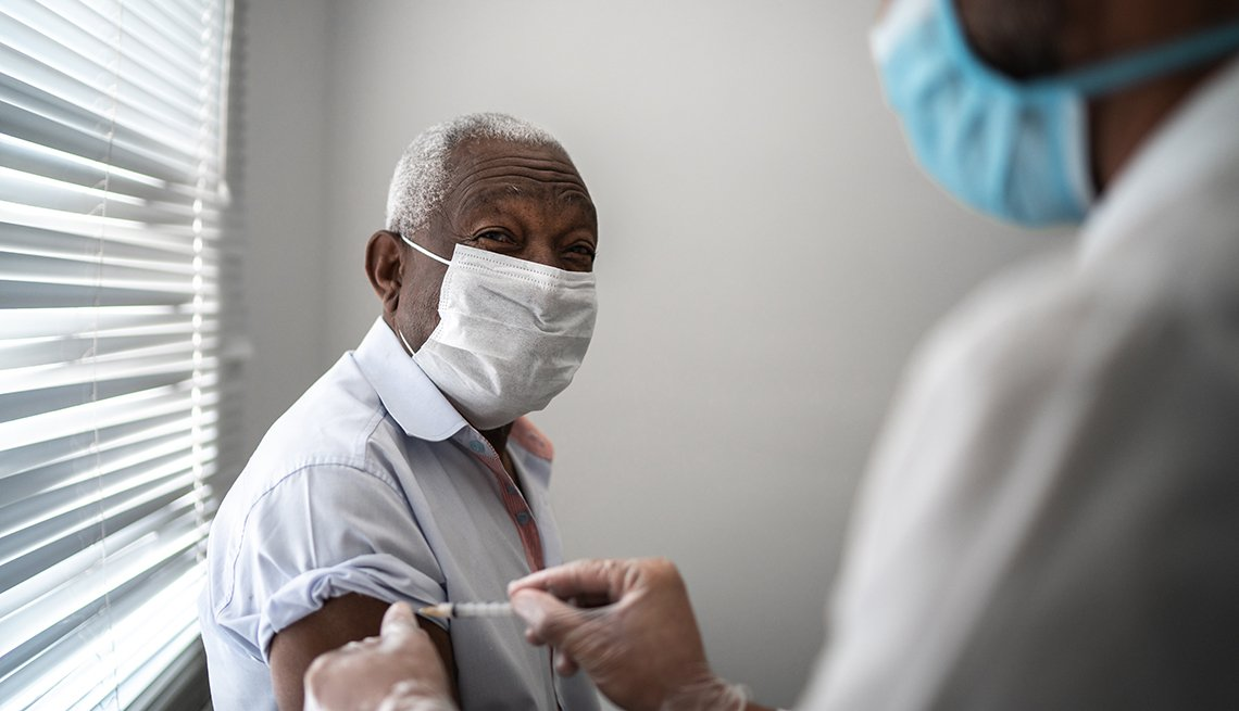 A nurse giving a male nursing home resident a vaccine shot in the arm