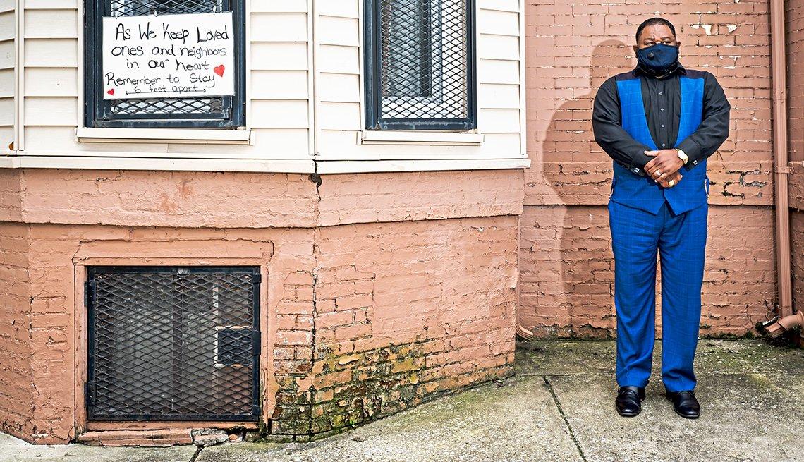 The reverend doctor derrick de witt stands outside a building wearing a mask