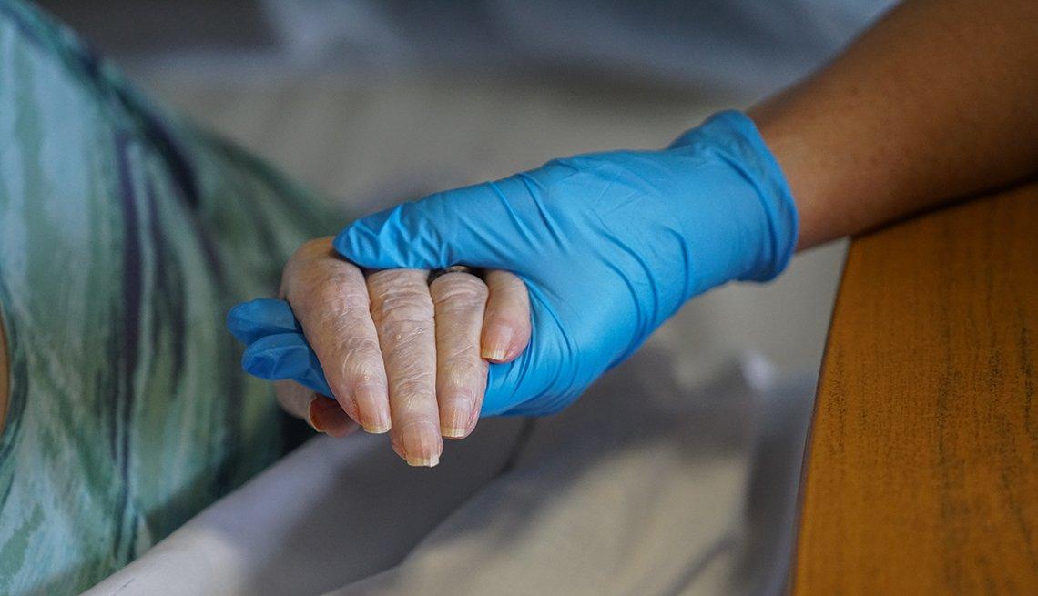 Una enfermera con un guante sostiene la mano del paciente.