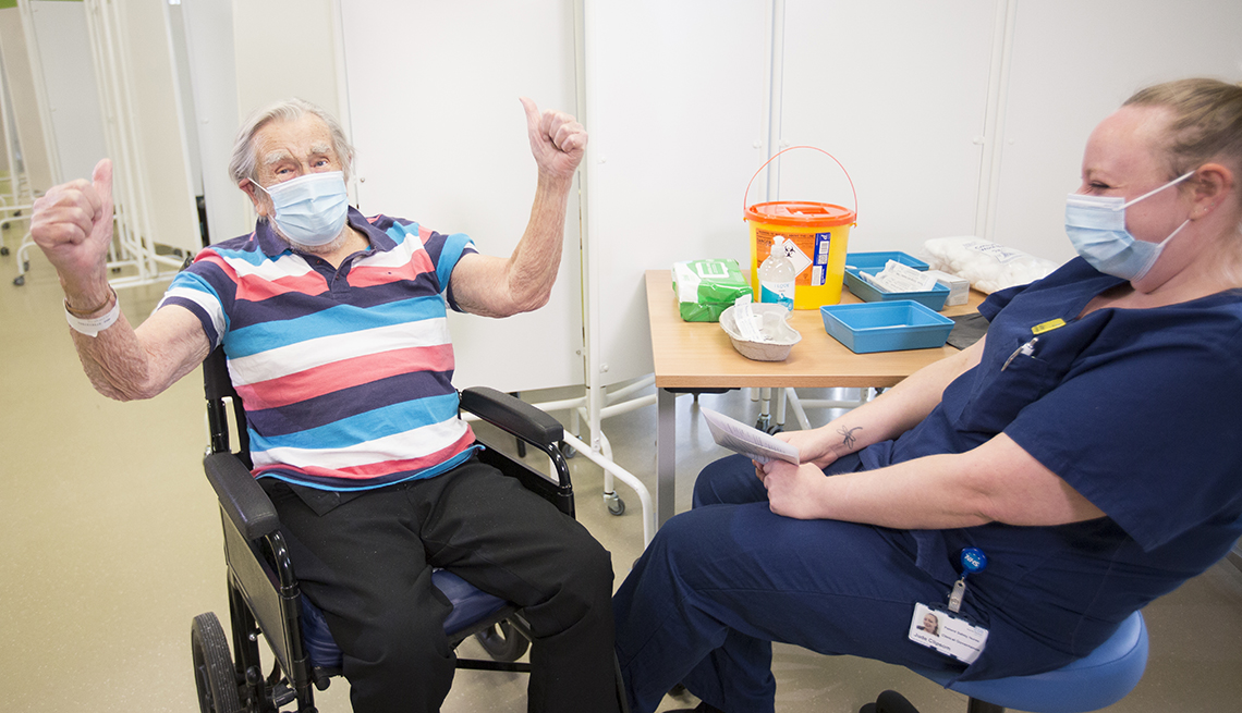 man in a wheel chair raising his hands in joy after receiving a coronavirus vaccine. a healthcare working sitting next to him is laughing