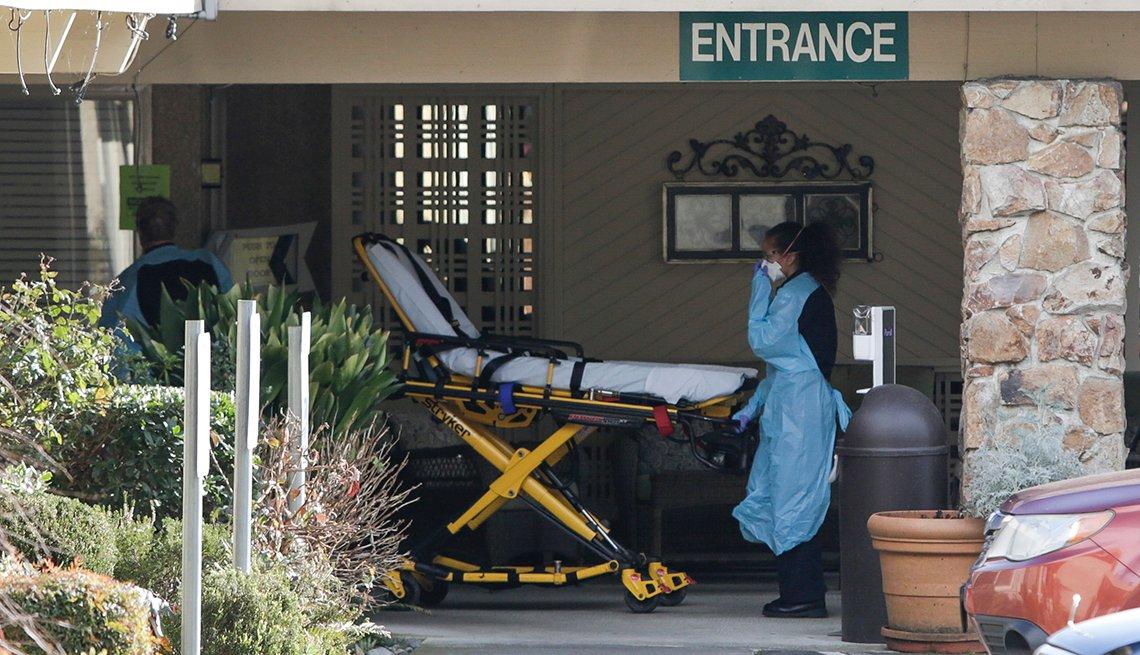 Personal de emergencia mueve una camilla para buscar un paciente en un hogar de ancianos.