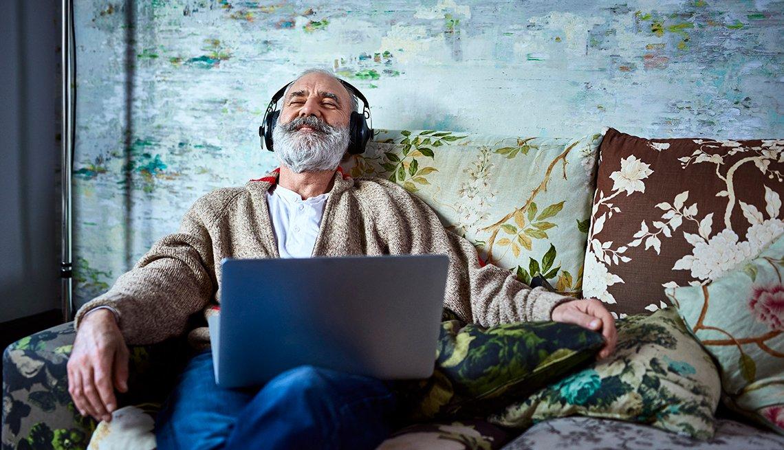 Cuidador de familia se relaja en su sofá escuchando música a través de auriculares.