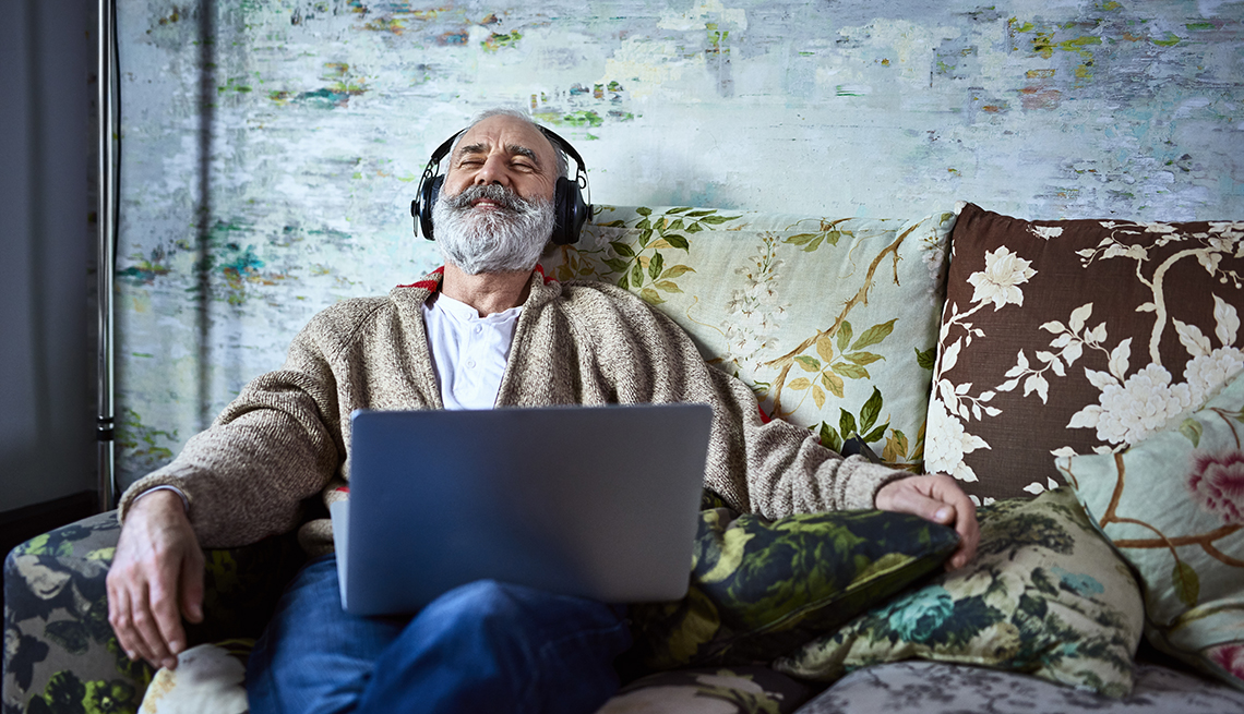 Male family caregiver relaxing on his couch listening to music through headphones