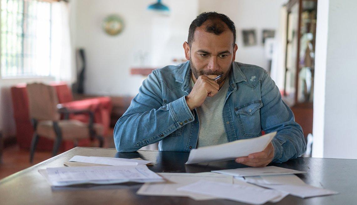 Un hombre de aspecto frustrado sentado en una mesa mirando a través de sus gastos y facturas.