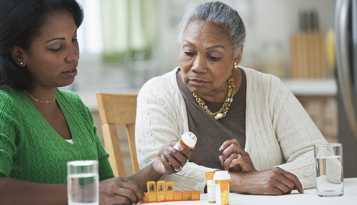 Una hija junto a su madre mirando frascos de medicamentos recetados.