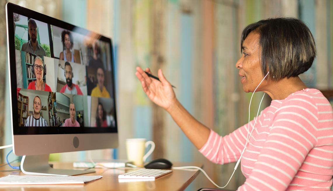 Una mujer cuidadora sentada en un escritorio trabajando durante una llamada de videoconferencia.