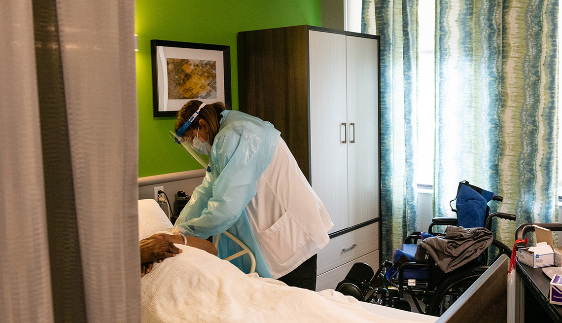 A nursing home worker wearing p p e checks on a resident laying in bed