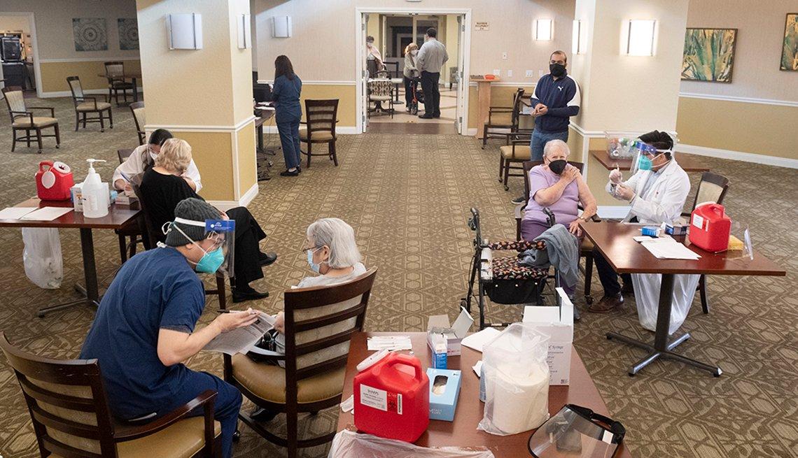 Tres residentes de hogares de ancianos en diferentes mesas recibiendo la vacuna contra la COVID-19.