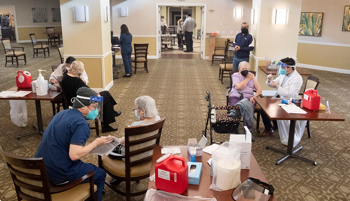 three nursing home residents at different tables getting covid vaccine shots