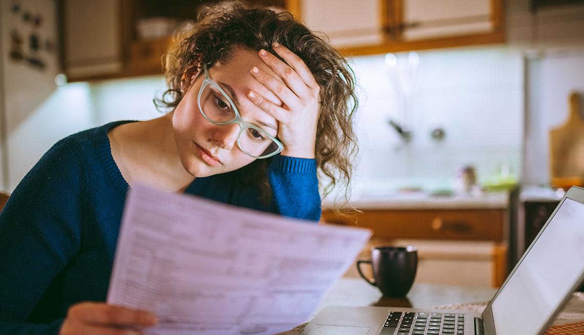 Una mujer sentada en una mesa mira una cuenta de cobro