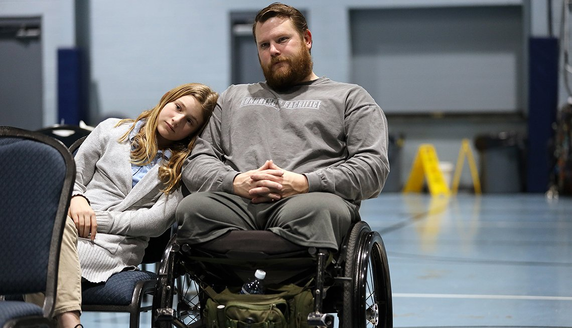 A man in a wheelchair sits next to a young girl