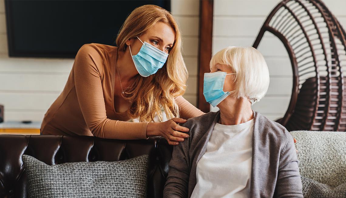 Un mujer con máscara médica es visitada por otra mujer.