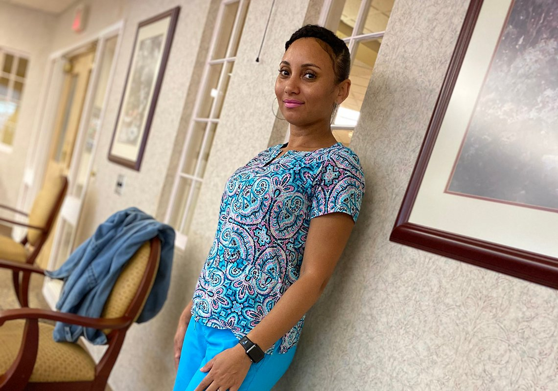 Asistente de enfermería certificada Adelina Ramos de pie en el pasillo de un hogar de ancianos.