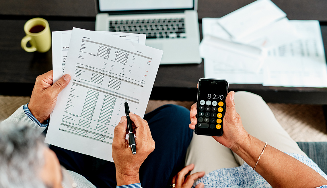 A top view of a couple doing their taxes. One person holds paperwork and one holds a calculator