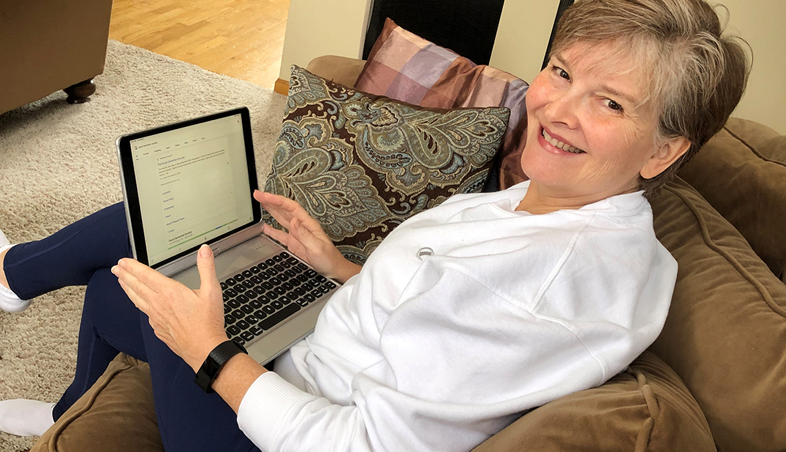 Kirby on her couch using a laptop