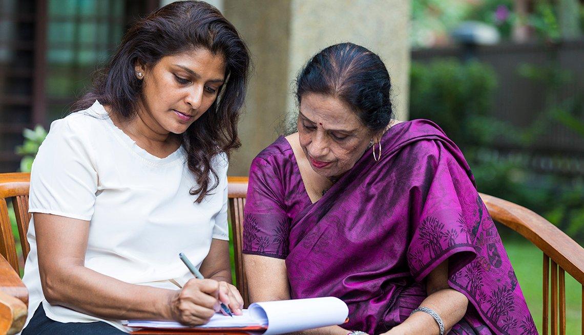 Una mujer sentada con su madre llenando el papeleo para convertirse en la representante legal de su madre.