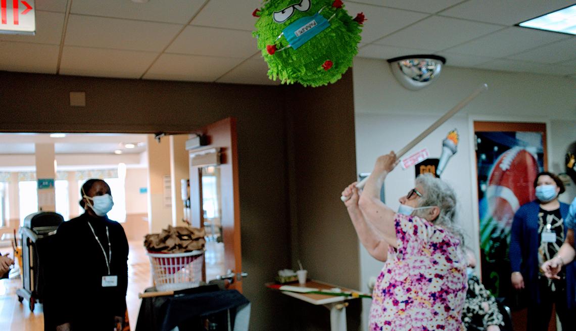 A female nursing home resident swinging a stick at a virus bug shaped piñata