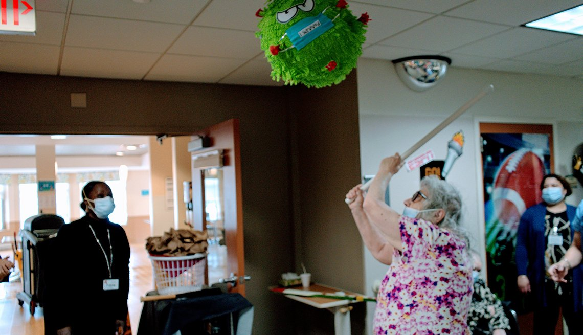 A female nursing home resident swinging a stick at a virus bug shaped piñata
