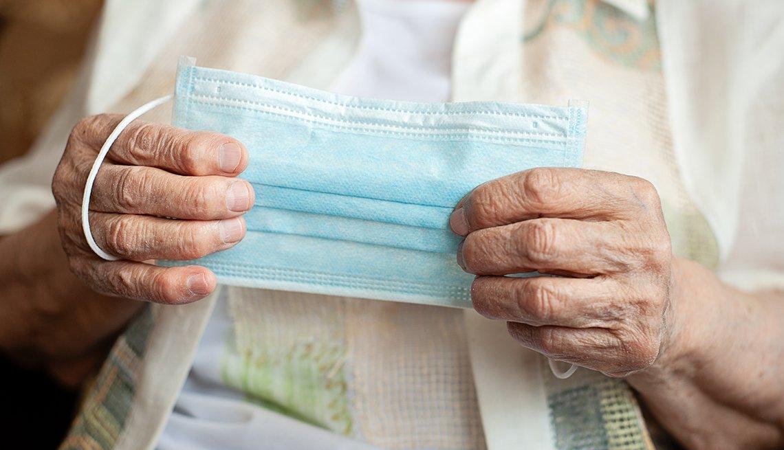 Manos de una mujer mayor que sostienen una mascarilla