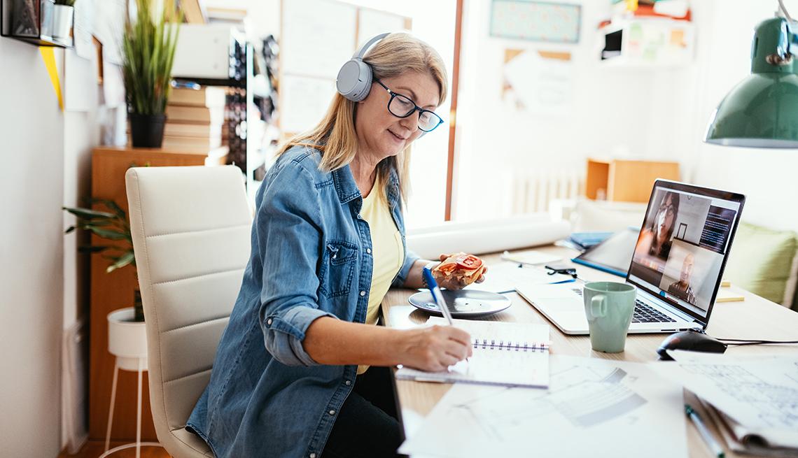 Mujer madura que trabaja desde casa en la computadora portátil. La mujer tiene planos sobre la mesa, trabajando con inversiones y finanzas.