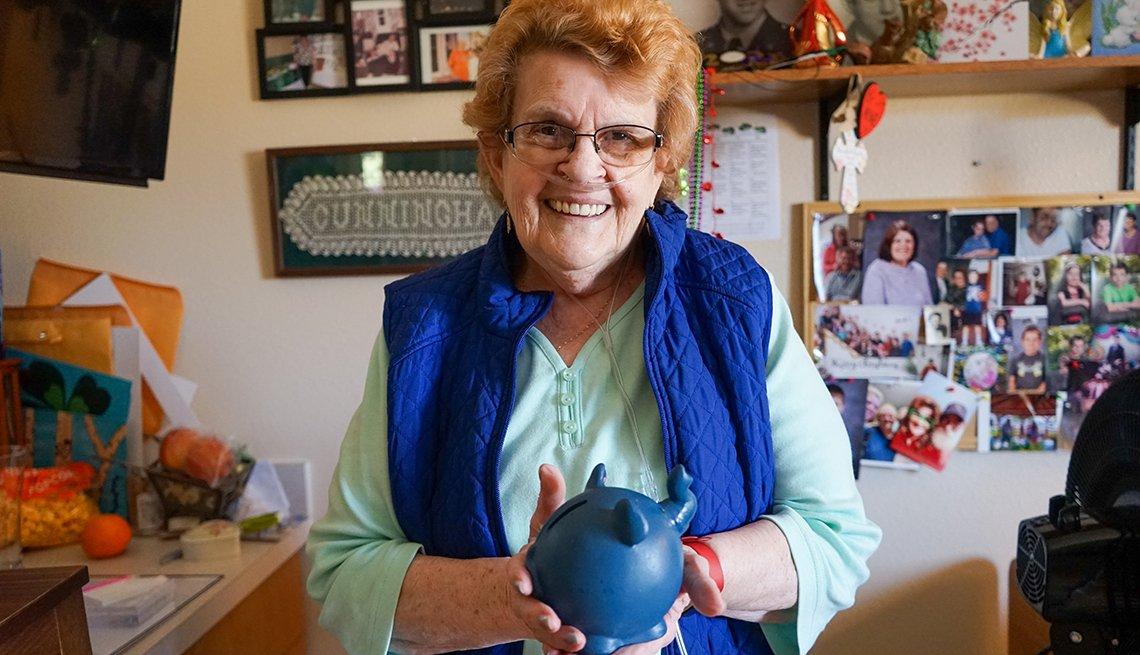nursing home resident alice cunningham holding a piggy bank