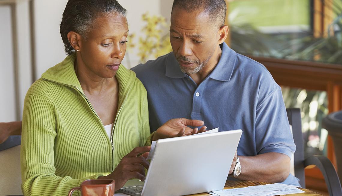 Una pareja sentada en una mesa con una computadora mirando facturas médicas y luciendo estresada.