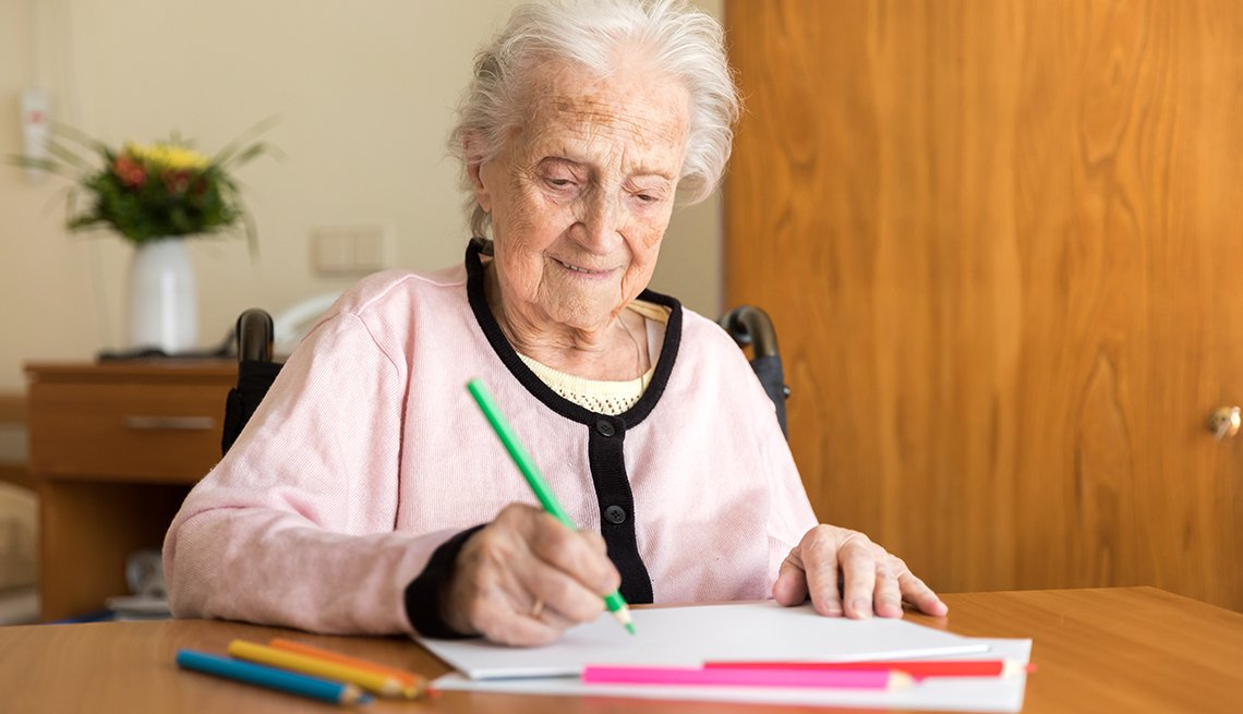 A woman with dementia drawing with colored pencils