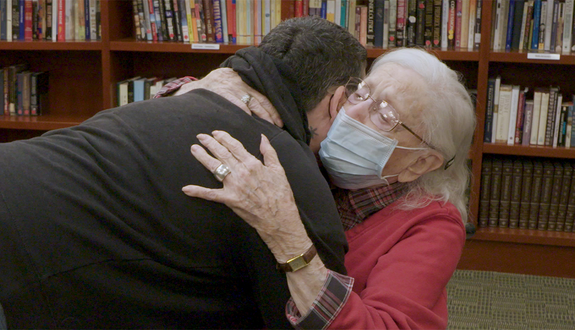 a nursing home resident wearing a face mask hugs her daughter