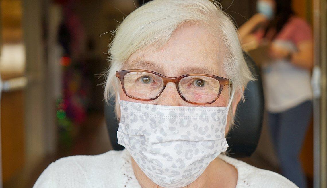 La residente Frieda Waterson sonríe bajo su mascarilla durante una visita con su familia.