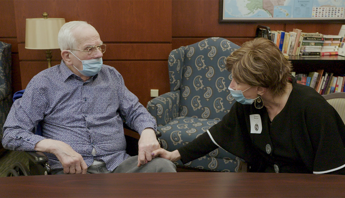 a nursing home resident holding his wife's hand during a visit