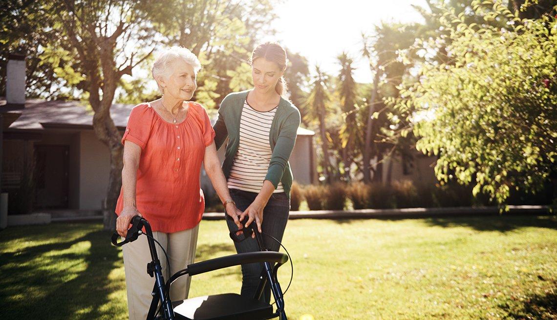 Una mujer que usa un andador afuera mientras su hija adulta la ayuda.