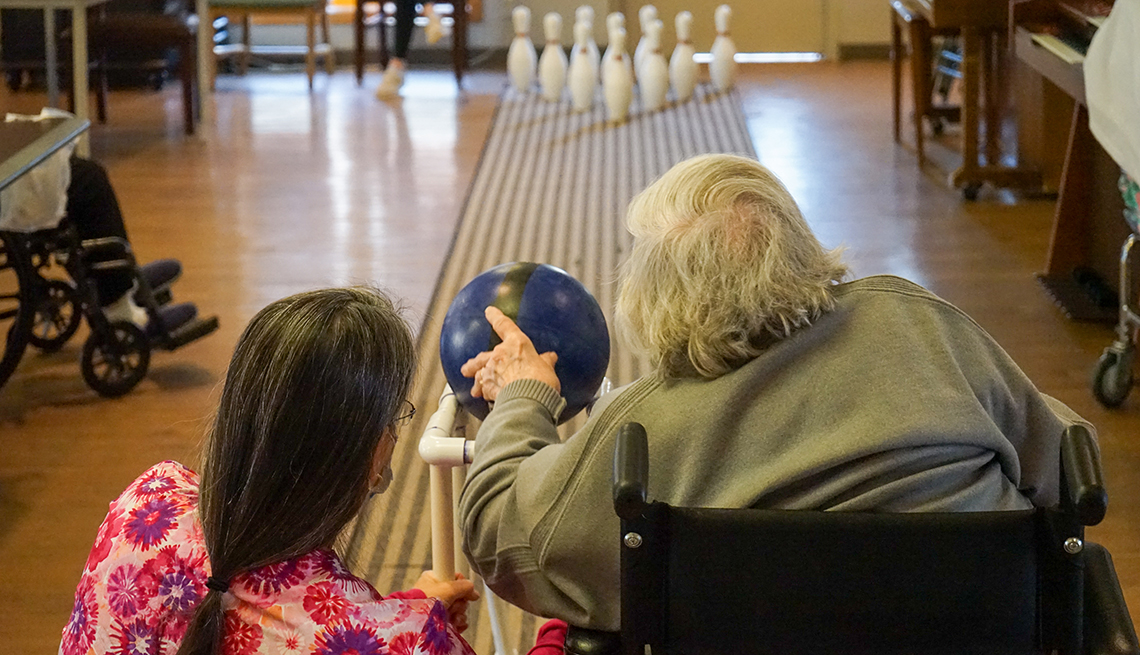 nursing home resident janice whitley bowling with the help of  an aide