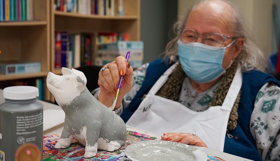 """La residente Norma Reman pinta a su cerdo, """"Porky"""", en una clase grupal de cerámica."""
