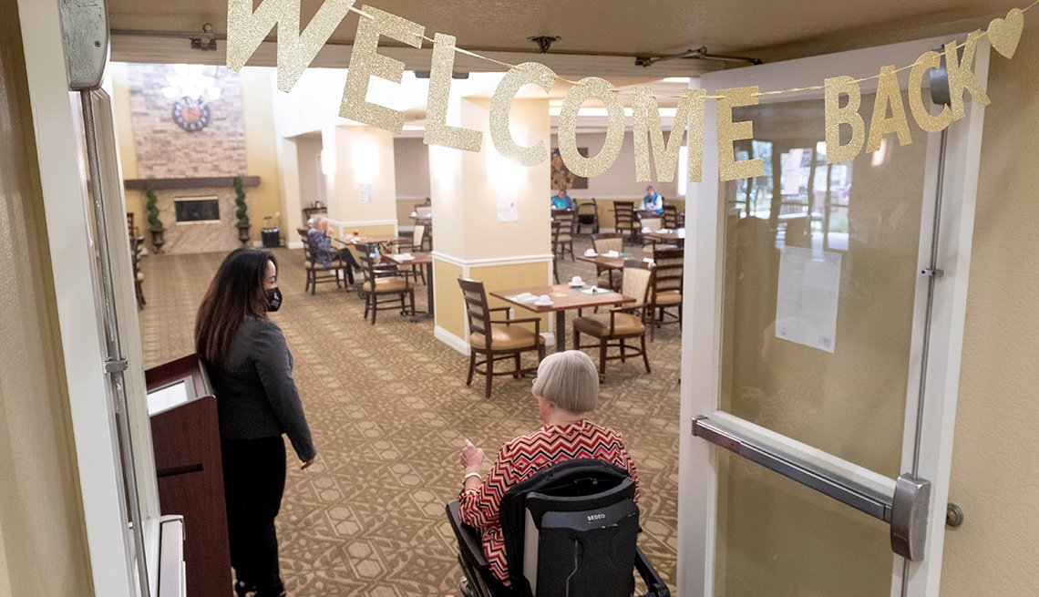 """Un residente de un hogar de ancianos en una silla de ruedas ingresa al comedor de un hogar de ancianos bajo un cartel que dice """"Bienvenido""""."""