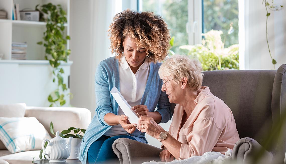 Un cuidador sostiene una hoja de papel que ayuda a una mujer a revisar sus opciones para pagar el cuidado a largo plazo.