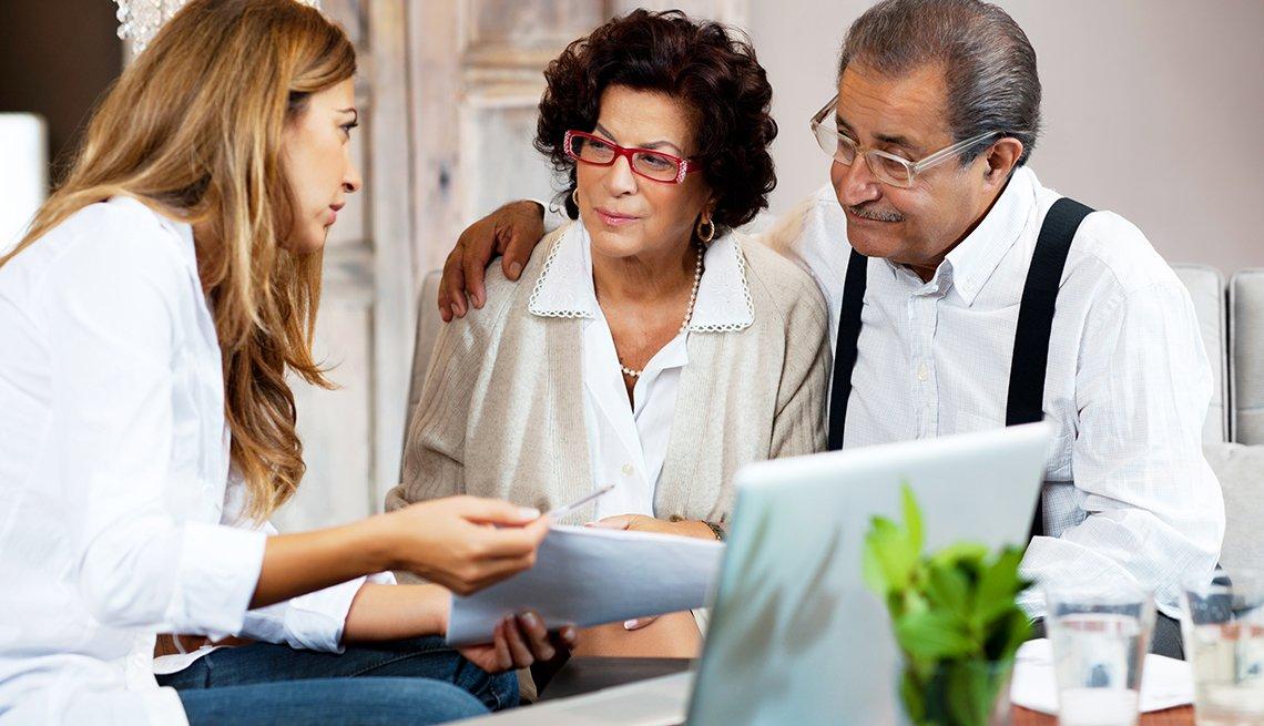 Una pareja sentada con un abogado que documenta sus directivas anticipadas.