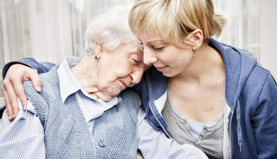 Una mujer mayor reclina cariñosamente su cabeza sobre el hombro de una mujer más joven.