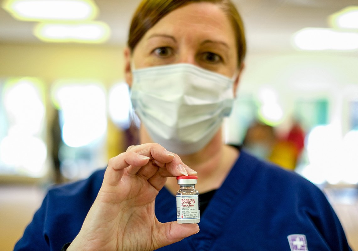 a nurse holds a vaccine vial