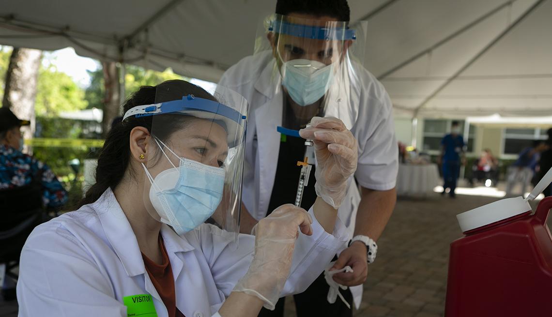Trabajadores de la salud se preparan para poner una vacuna a un paciente.