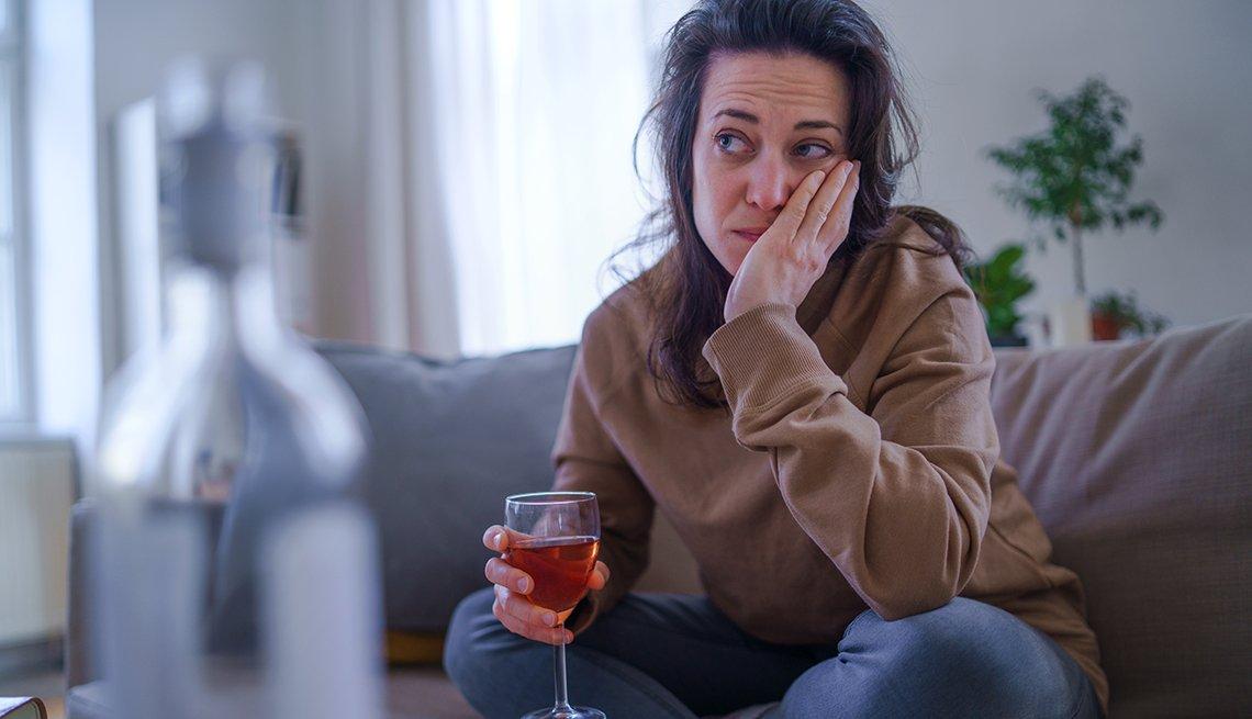 Una mujer que cuida a la familia sentada en su sofá con una copa de vino con aspecto estresado.