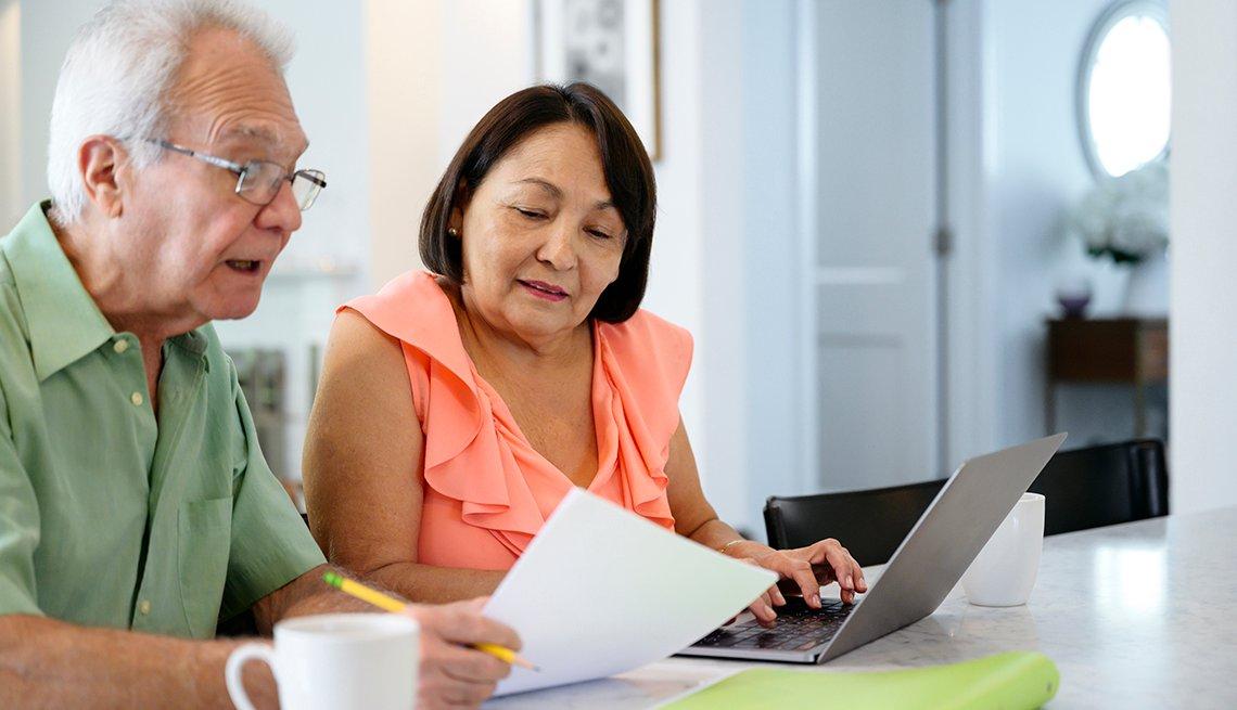Una pareja revisando sus finanzas haciendo un presupuesto para los gastos de atención a largo plazo.