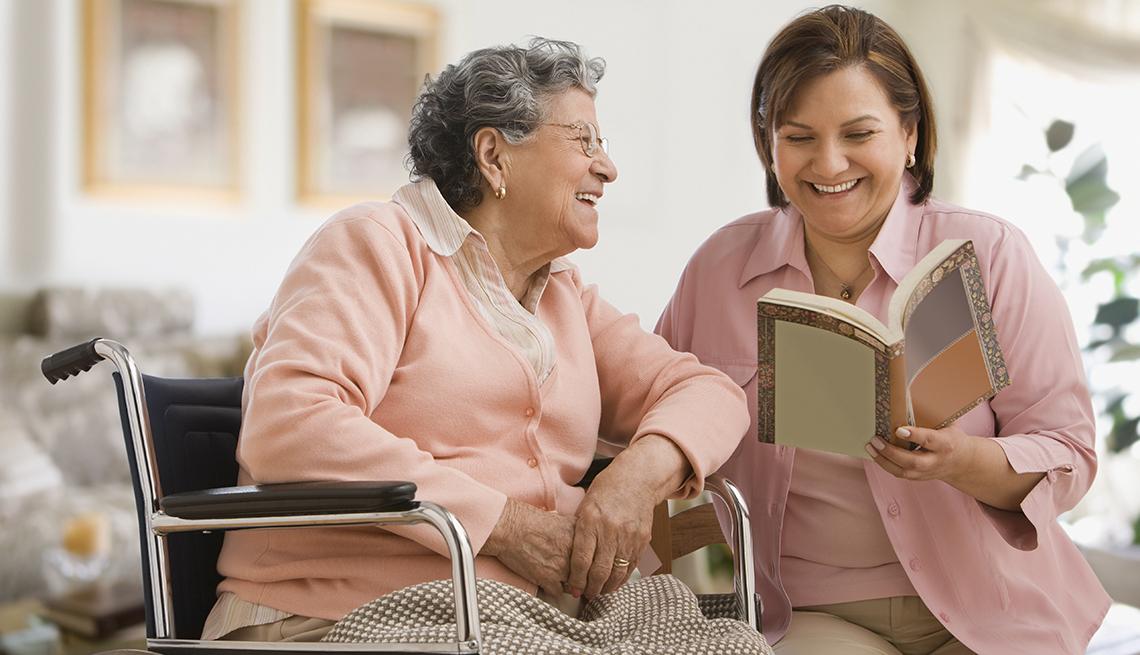 Una mujer leyendo un libro a su madre que está sentada en una silla de ruedas.