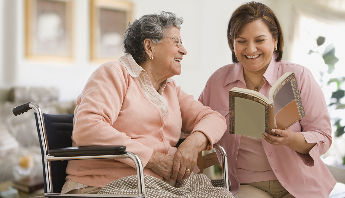 A woman reading to her mother who is sitting in a wheel chair