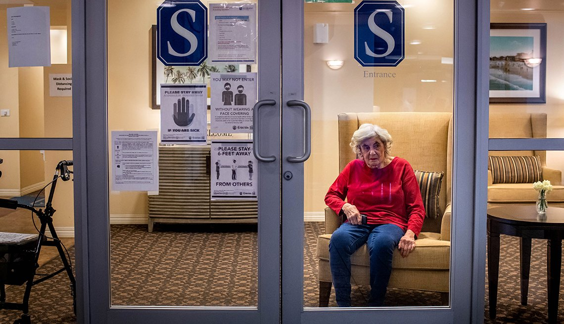 Woman sitting behind class doors of a nursing home with covid warning signs posted