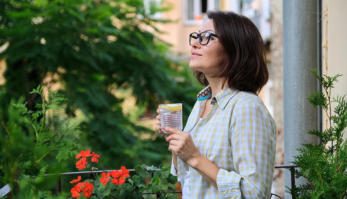 Mujer de pie mirando la naturaleza relajada mientras toma agua con limón.