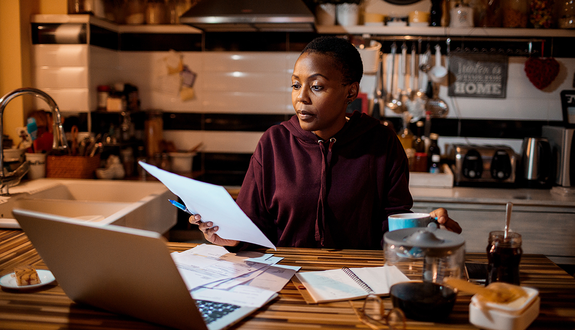 a woman sitting at a laptop and looking through bills looking stressed