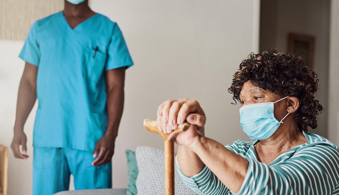 Una mujer residente de un hogar de ancianos sosteniendo un bastón y usando una mascarilla con un trabajador de un hogar de ancianos en el fondo.