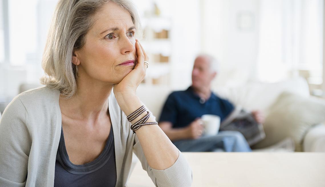Una cuidadora que parece estresada mientras su esposo se relaja en el sofá detrás de ella.